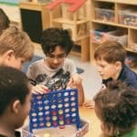 School age boys playing connect four game