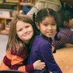 two school age girls side by side
