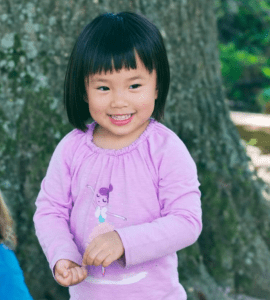 little girl in violet shirt in front of tree