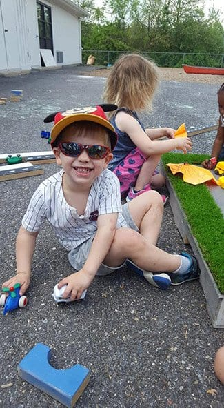 boy plays with toys at our preschool