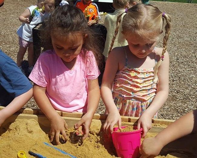 girls playing in a sandbox