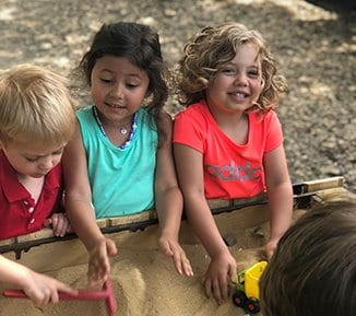 kids playing in a sandbox at our childcare center
