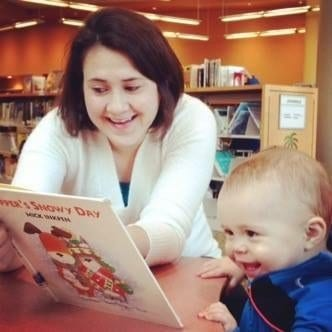 Teacher reading to a toddler at our childcare center