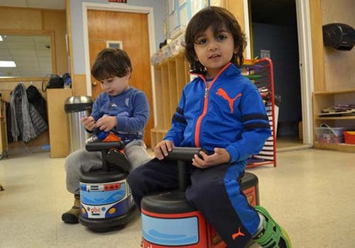 Two year olds riding cars at our preschool center