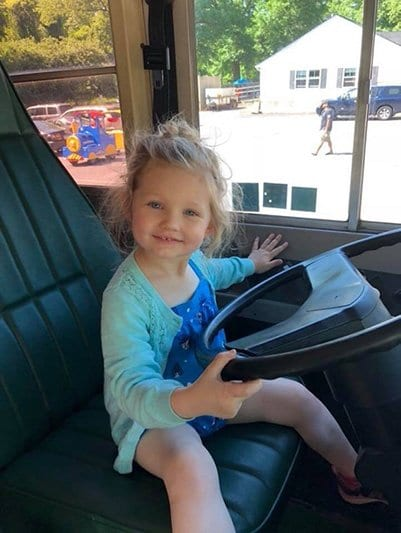 child sitting in the bus drivers seat at our childcare center