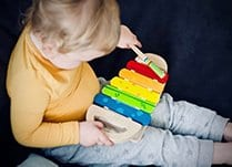 Toddler playing with a xylophone