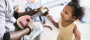 child fascinated by a ukulele