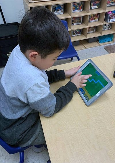 child using a tablet at coding camp