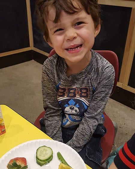 boy eating fruit and veggie at daycare
