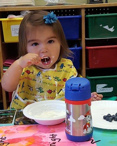 girl eating fruit and yogurt at preschool