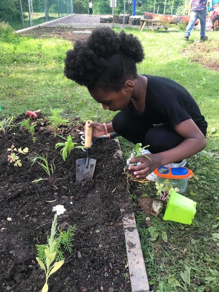 girl prepping soil for flowers in garden