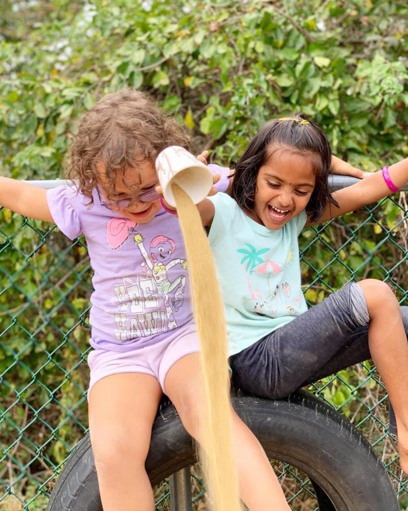two girls playing with sand in garden