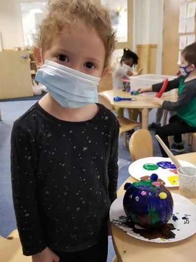 girl with mask on at preschool center