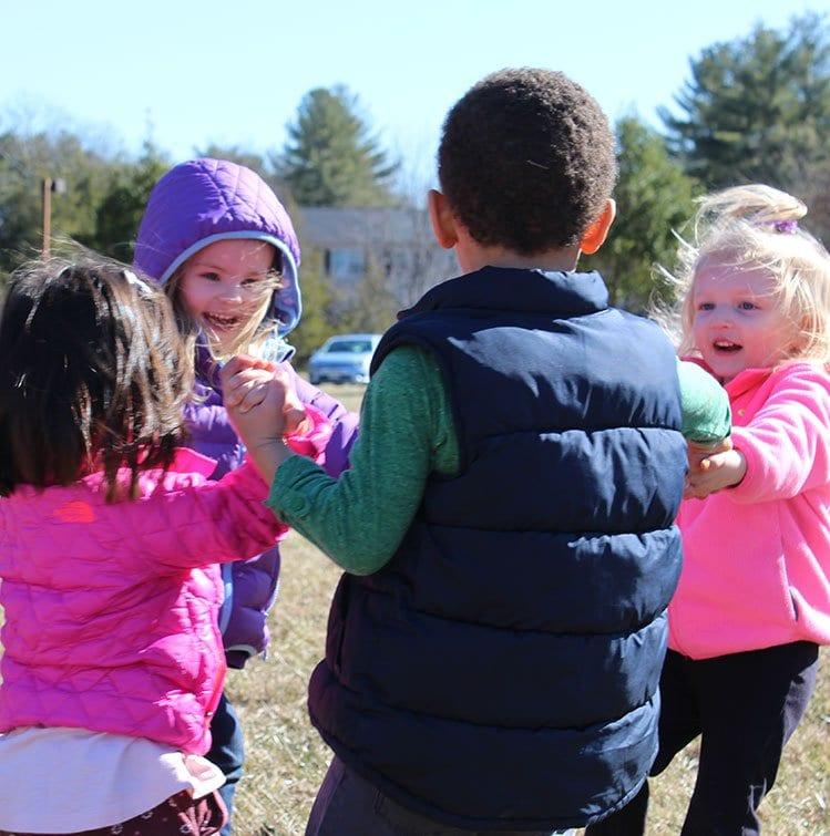 children holding hands outside at preschool
