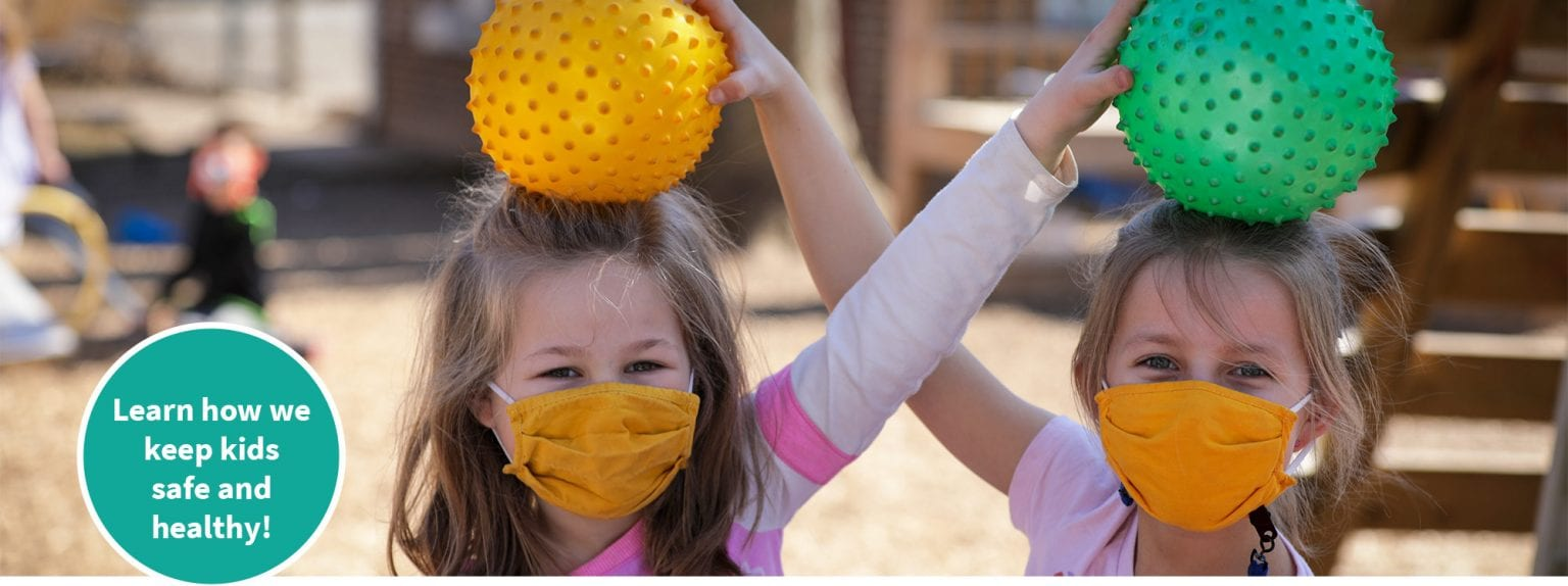 girls playing outside on playground at preschool homepage banner2